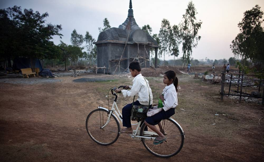 Cambodian school children make their way past the tomb of former Khmer Rouge leader Ta Mok in Anlong Veng, Cambodia