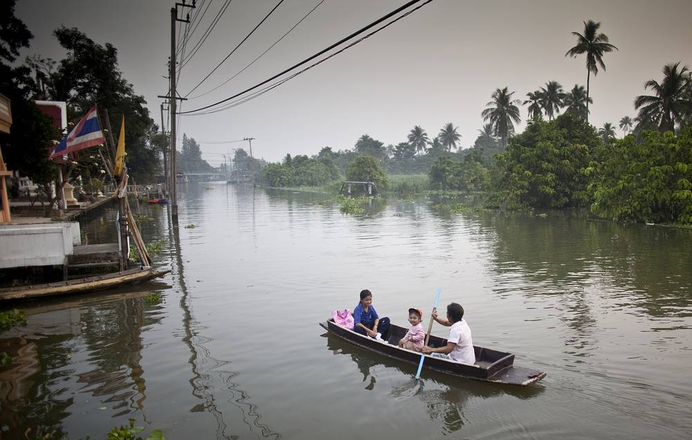 A Thai woman paddles children to school along Bangkok Noi Klong on the outskirts of Bangkok, Thailand