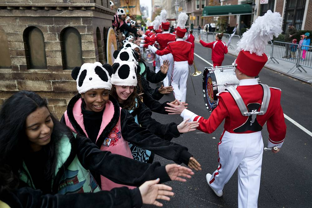 Participants greet others as they await the start of the Macy's Thanksgiving Day Parade in New York, USA, November 24