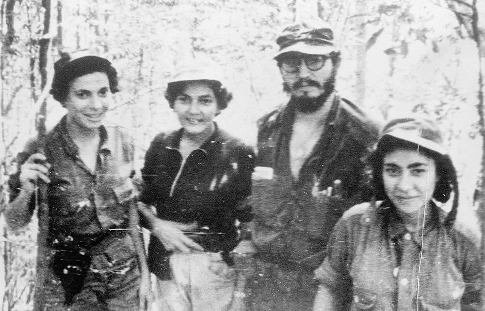 "In November 1958, Fidel Castro personally led his forces into battle near Guisa, not far from the island's second most important city of Santiago de Cuba. It was the start of the rebel army's final offensive. Photo: Cuban rebel leader Fidel Castro and nurses who worked for the rebel army ""Movement 26th July"" in the Sierra Maestra, Cuba, 1958"