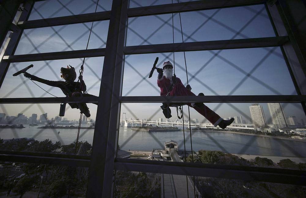 Window cleaners dressed as Santa Claus and a reindeer cleaning windows at a shopping mall in Tokyo's Daiba bay area, December 21