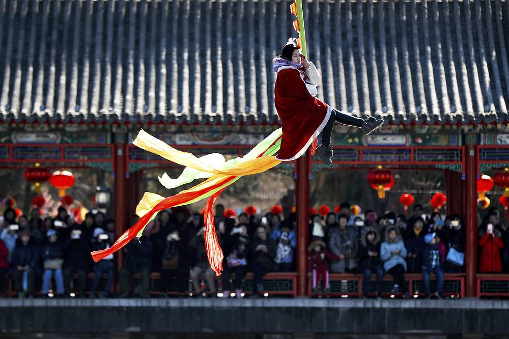 Visitors to a temple fair watch a Chinese acrobat dressed in traditional costumes perform during the Lunar New Year celebrations in Beijing, China, February 1