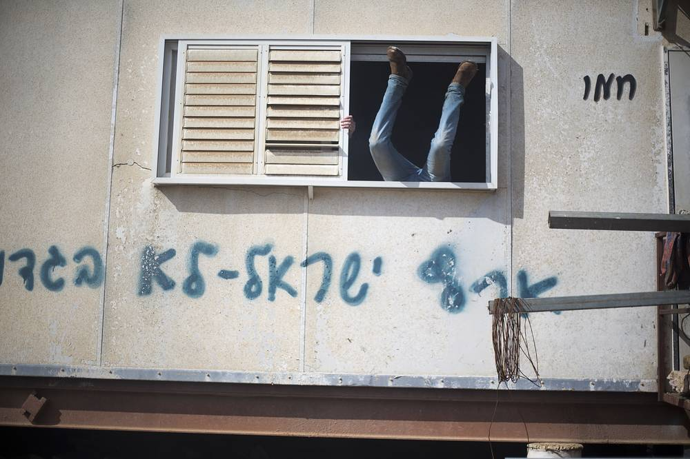 A settler jumps into a trailer in Amona outpost in the West Bank, as Israeli forces evacuate a controversial settlement, February 1
