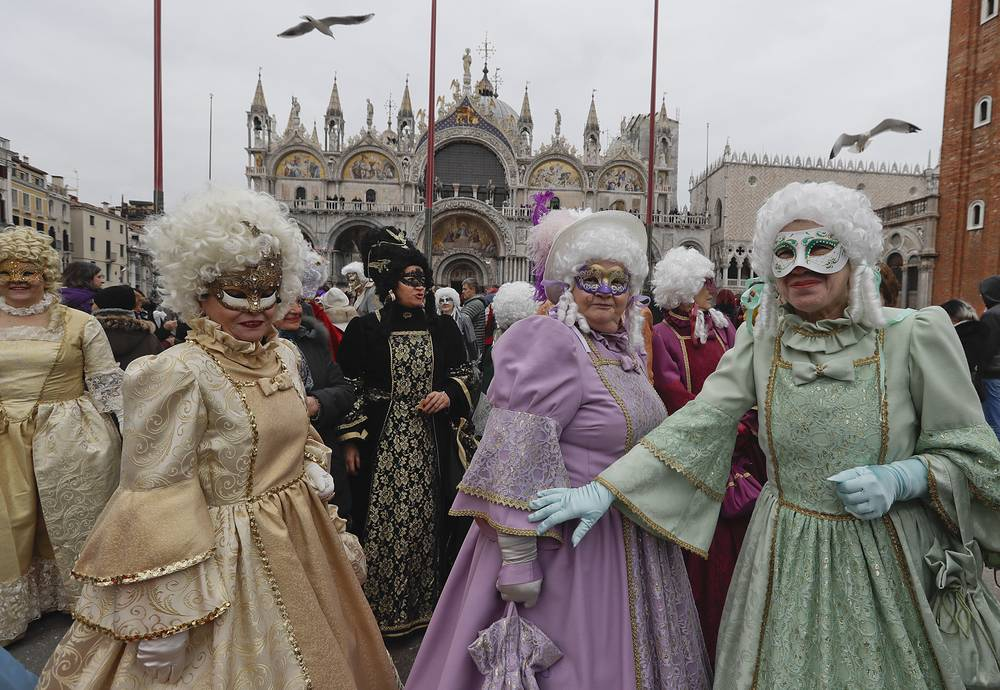 People wearing carnival costumes and masks gather in St. Mark's Square during carnival celebrations in Venice
