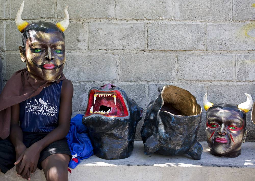 A masked performer waits for his friends before a Carnival parade in Les Cayes, Haiti, February 28