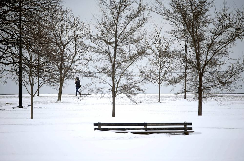 Man walks along Lake Michigan as the Chicago area gets it's first measurable snow since December, March 13, 2017
