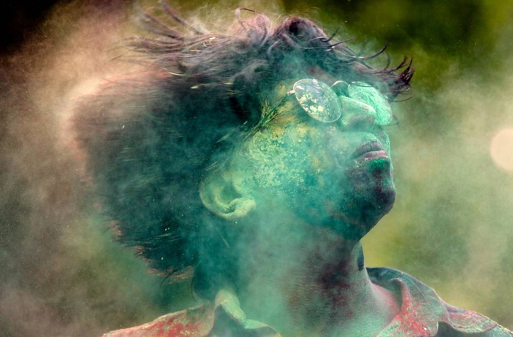 An Indian reveller covered with powdered colors celebrates the Holi festival in Bangalore, India, March 13