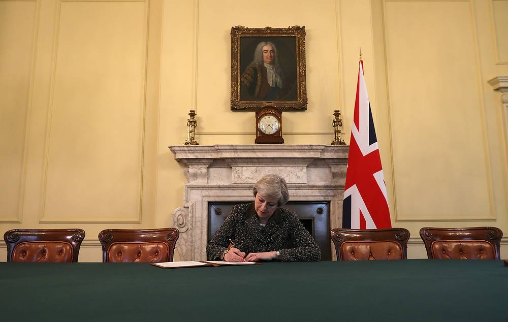 British Prime Minister Theresa May in the cabinet, sitting below a painting of Britain's first Prime Minister Robert Walpole, signs the official letter to European Council President Donald Tusk invoking Article 50 and the United Kingdom's intention to leave the EU, March 28