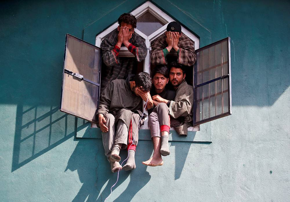 People sit in a window of a mosque during the funeral of Tauseef Ahmad Wagay, a suspected militant, who according to local media was killed in a gun battle with Indian army in Chadoora, south Kashmir's Kulgam district, March 29