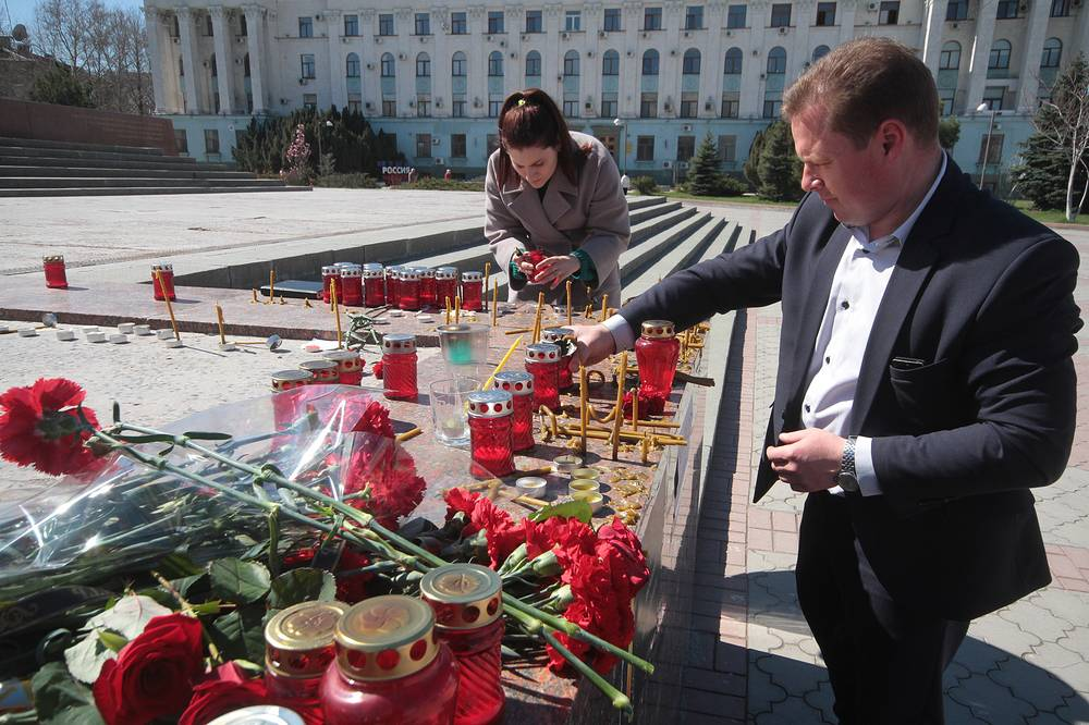 People light candles at an impromptu memorial in Lenin Square in Simferopol, Crimea