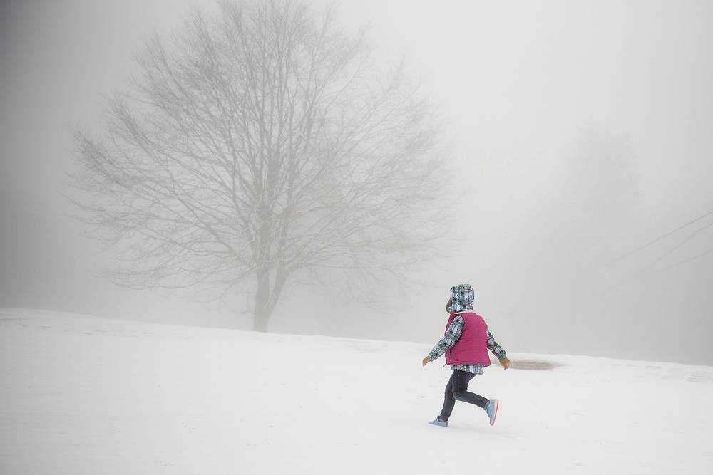 A child runs across a meadow covered in fresh snow on Mount Kekesteto, Hungary, April 18