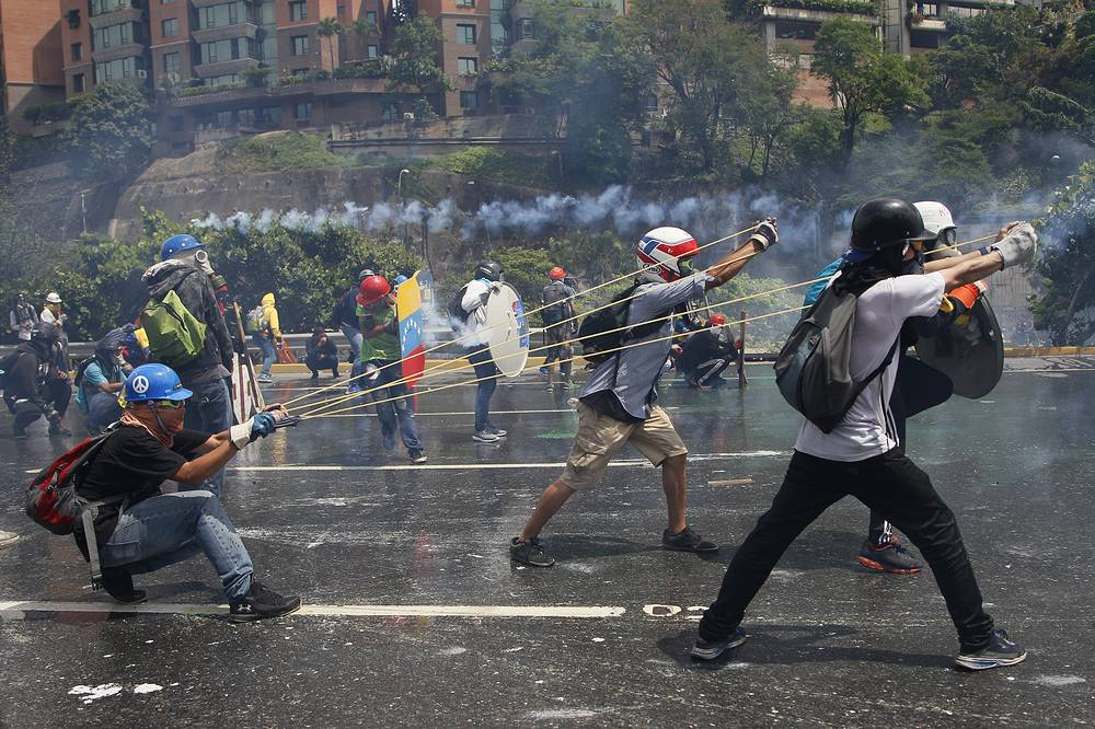 Anti-government protesters work together to aim a giant slingshot holding a glass bottle of fecal matter, at security forces blocking their march from reaching the Supreme Court in Caracas, Venezuela, May 10