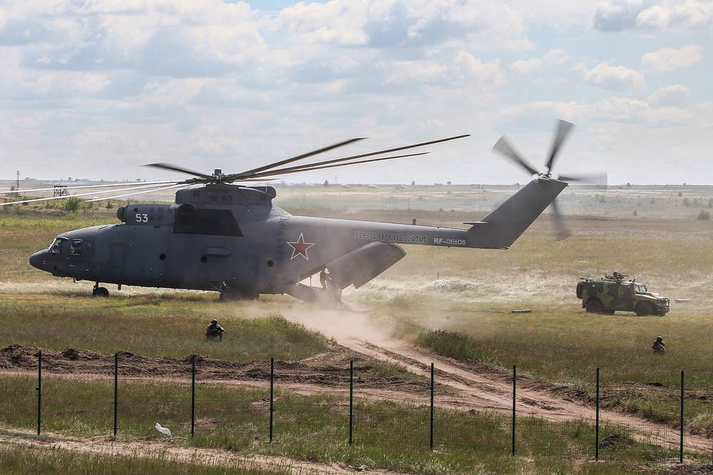 Mil Mi-26N heavy lift cargo helicopter lands a Tigr multipurpose infantry mobility vehicle