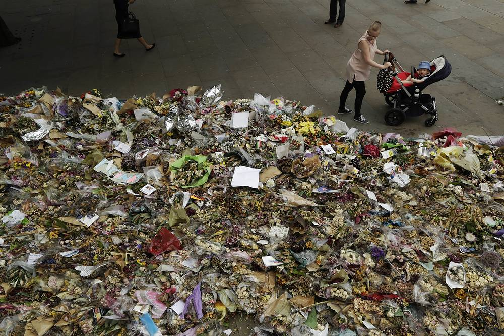 A woman with a young child looks at floral tributes at the southern end of London Bridge, where in a June 3 attack three men drove people down and then went on a stabbing rampage, in London, UK, June 20