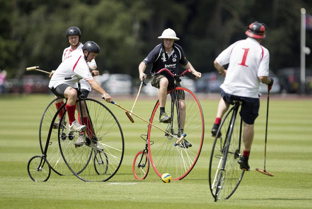 England team members in white shirts, compete against Scotland in the Penny Farthing International Polo fun match during the Bentley Motors Royal Windsor Cup Final in Windsor Great Park, England, June 25