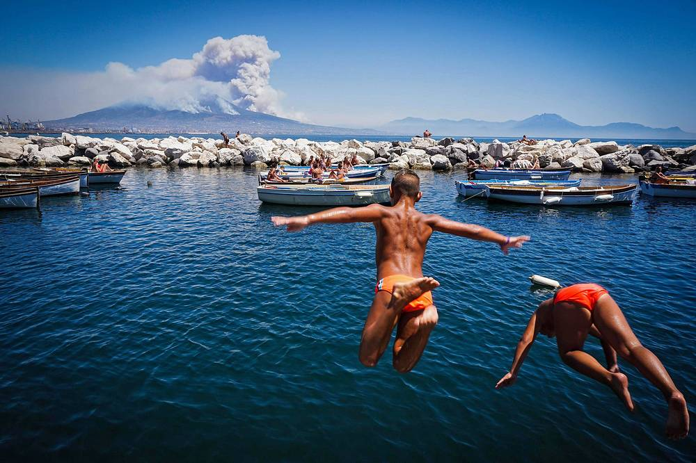 Children jump into the sea as smoke billows from fires around Mount Vesuvius volcano in Naples, Italy, July 11