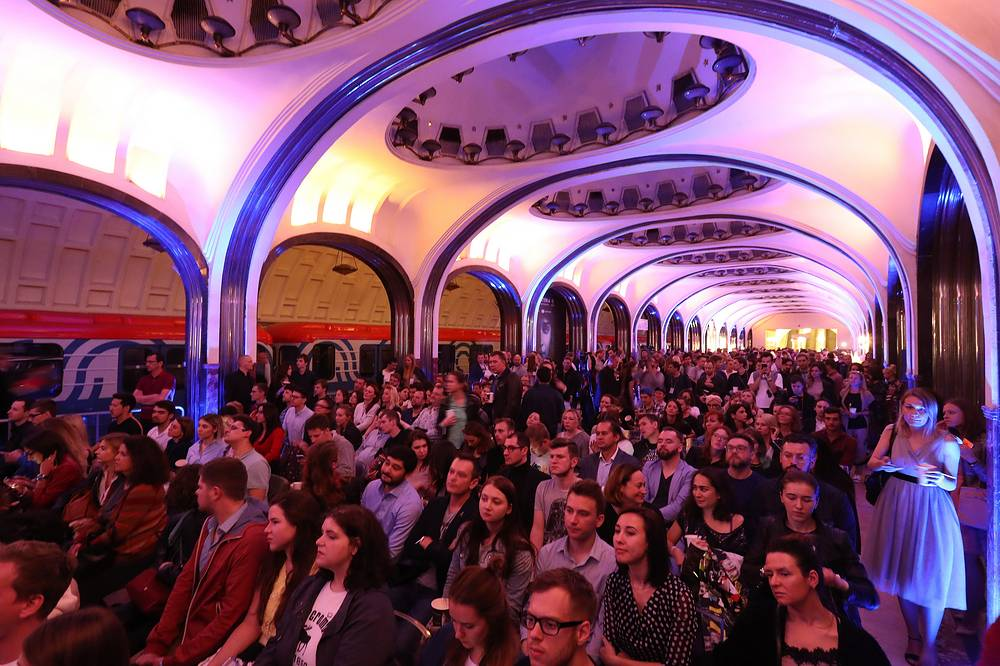 """Spectators watch the premiere of the """"Game of Thrones"""" television series at Mayakovskaya subway station in Moscow"""