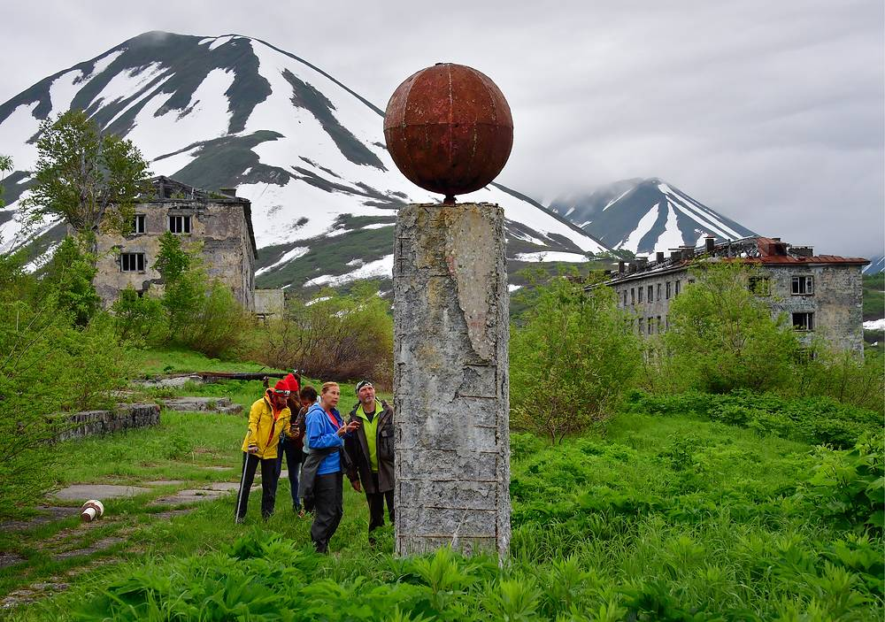 Tourists visit an abandoned garrison settlement by the Bechevinskaya Bay