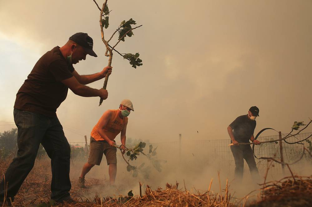 Men trying to extinguish flames approaching houses in the village of Sao Jose das Matas, near Macao, Portugal