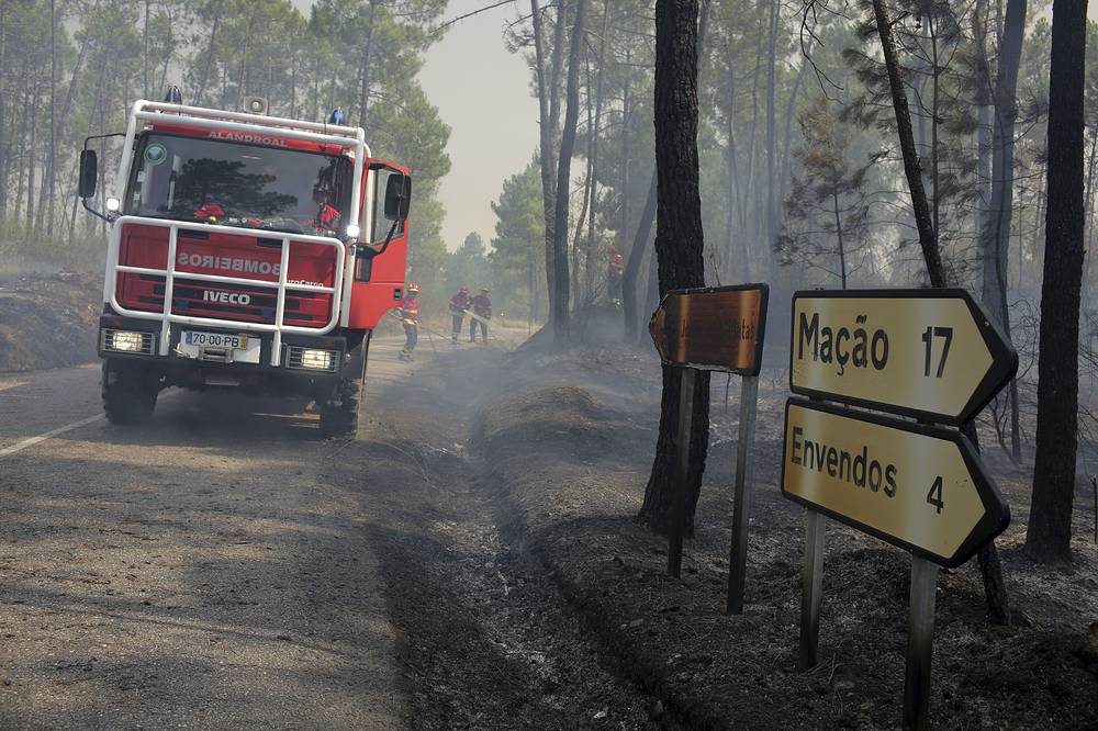 Firefighters work to prevent a fire from crossing a road near Macao, central Portugal