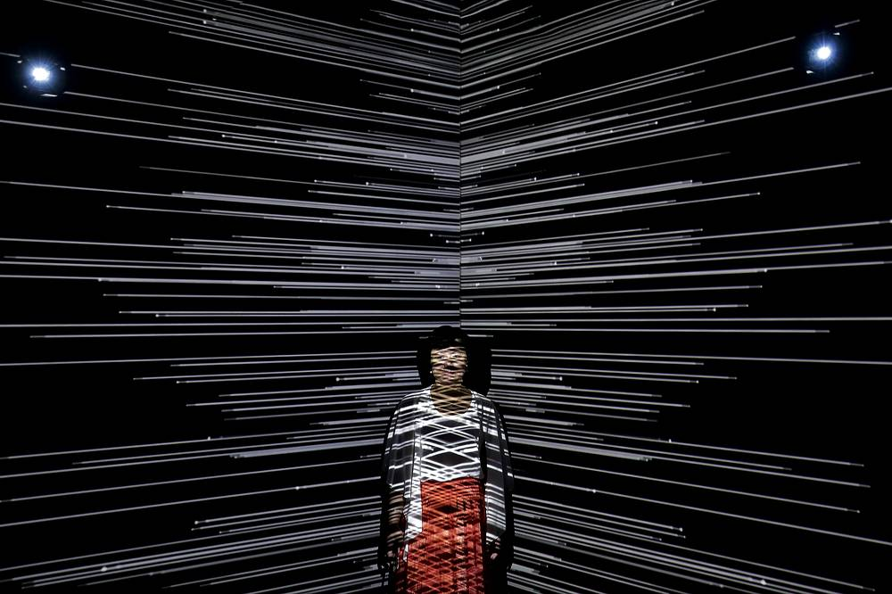 "A woman is beamed by light at an art installation titled ""Infinity Room"" displayed during The Future of Today Exhibition at Today Art Museum in Beijing, China, August 9"
