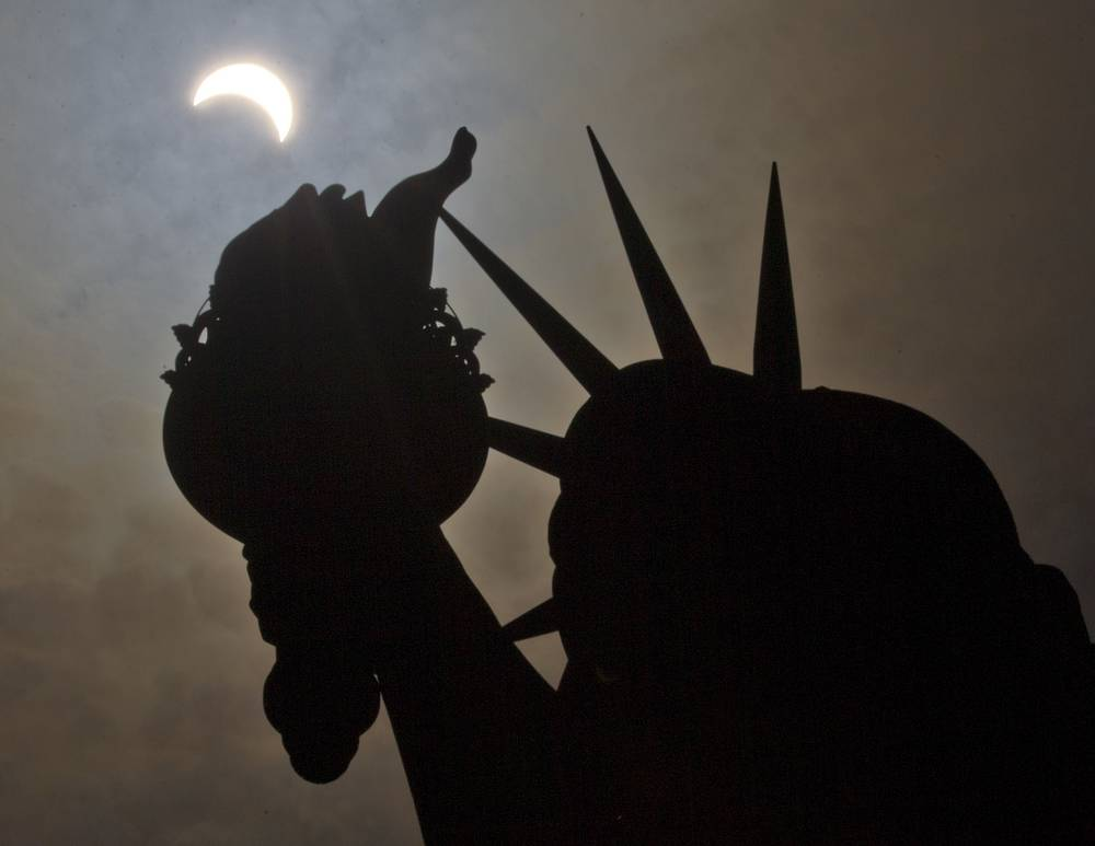 A partial solar eclipse seen near the Statue of Liberty on Liberty Island in New York