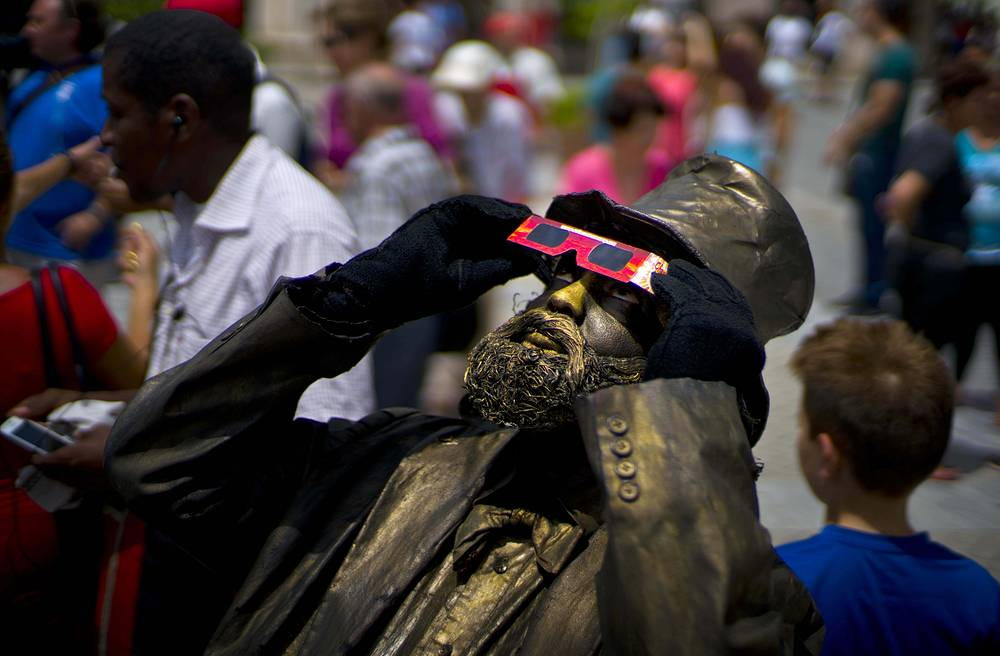 A street artist dressed as a bronze statue uses special glasses to view a partial solar eclipse in Havana, Cuba, August 21