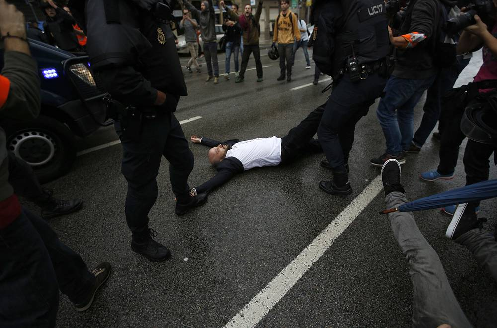 Spanish National Police drags away a man lying on the street as they try to prevent voters from reaching a voting site in Barcelona