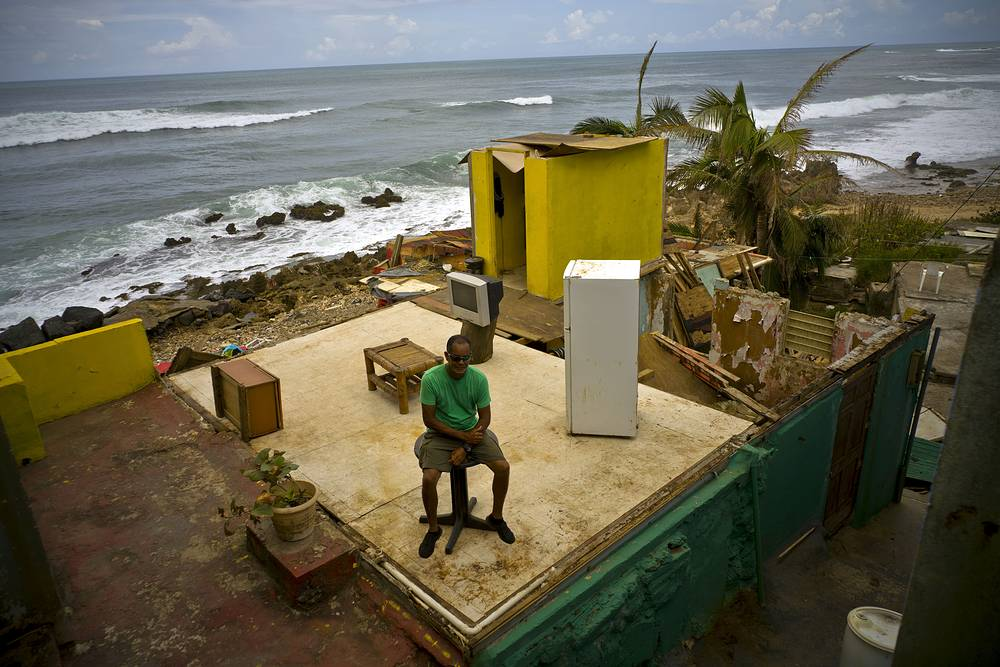 A local resident sits on a small table in his home that was destroyed by Hurricane Maria in La Perla neighborhood on the coast of San Juan, Puerto Rico, October 5