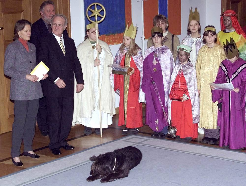 German President Johannes Rau, his wife Christina and their half-breed dog named Scooter listen to the holy star singers during a visit in the Berlin Presidential residence, 2001