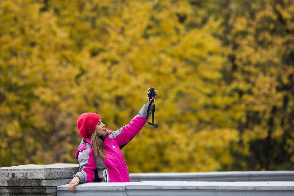 A tourist makes a selfie with autumn trees in Moscow's park