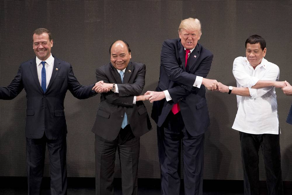 """US President Donald Trump does the """"ASEAN-way handshake"""" with Russian Prime Minister Dmitry Medvedev, Vietnamese Prime Minister Nguyen Xuan Phuc and Philippine President Rodrigo Duterte during the opening ceremony at the ASEAN Summit in Manila, Philippines, 2017"""
