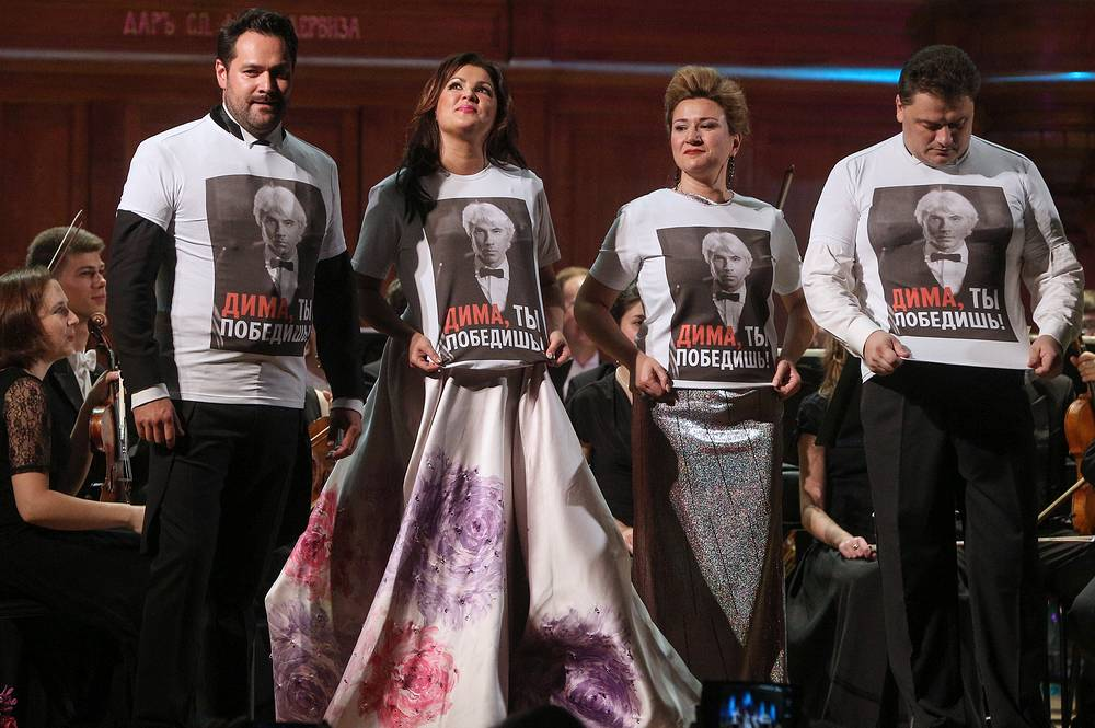 "Russian bass Ildar Abdrazakov, Russian soprano Anna Netrebko, Russian mezzo-soprano Ekaterina Gubanova, and Latvian tenor Aleksandrs Antonenko wearing T-shirts with a portrait of Dmitri Hvorostovsky and a sign reading ""Dima, you will win"" during a concert featuring international opera stars in the Grand Hall of the Moscow Conservatory, 2015"
