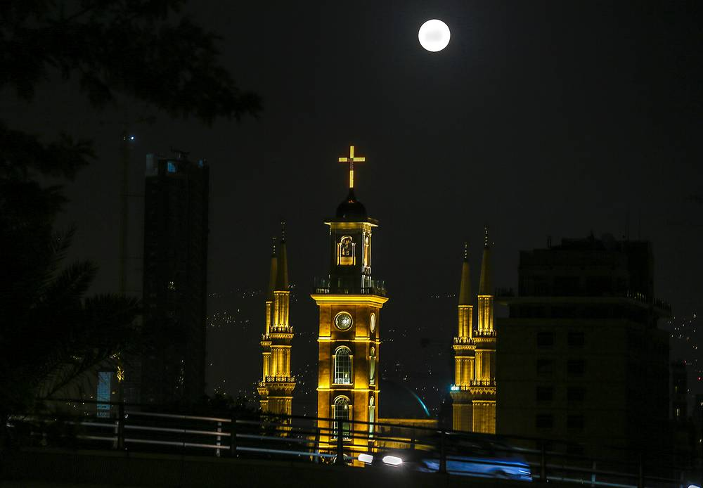 The full moon is seen on the sky over Al-Ameen Mosque and St. Gregory church, Beirut, Lebanon