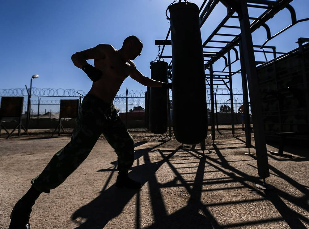 A Russian soldier punching a punch bag while training at an outdoor gym at Hmeymim airbase, February 24, 2016