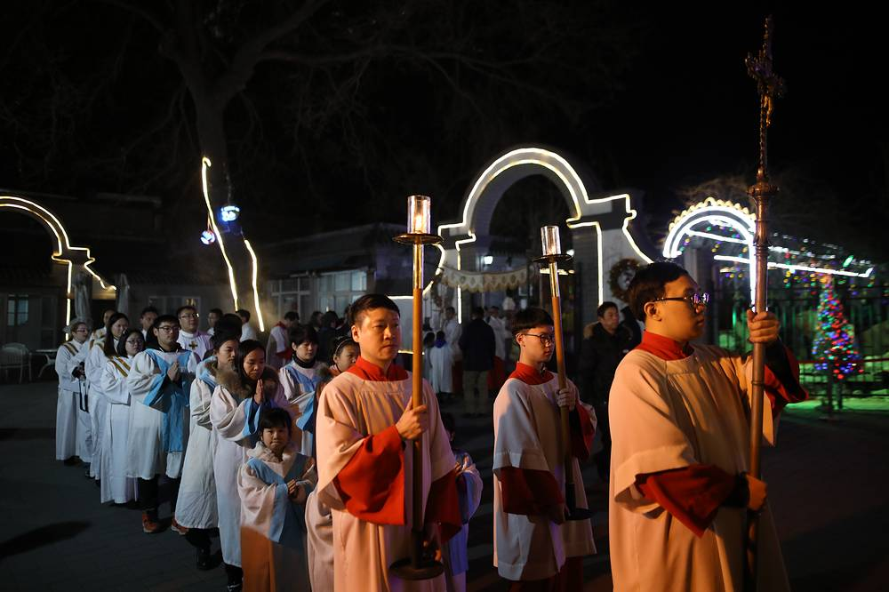 Cross-bearers march during the Christmas Eve mass in the Xuanwumen Catholic Church in Beijing, China