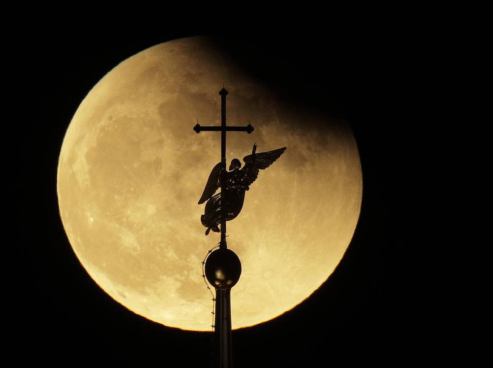 The city landmark weather vane in the form of an Angel, fixed atop a spire of the Saints Peter and Paul Cathedral, is silhouetted against the moon partially covered by earth's shadow during a lunar eclipse in St.Petersburg, Russia, January 31