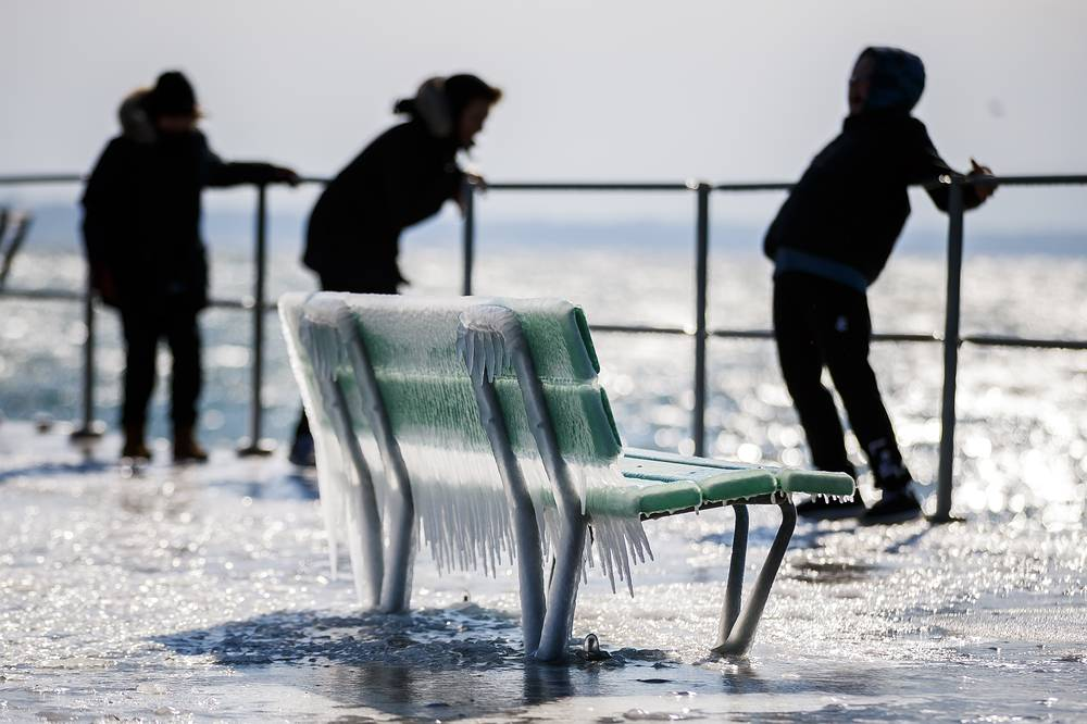 Kids play behind an icy bench on the frozen shore of Lake Geneva during a windy winter day, in Nyon, Switzerland