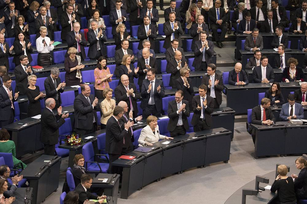 Members of the Bundestag applause German Chancellor Angela Merkel after her re-election during the election of the Federal Chancellor at the Bundestag in Berlin, Germany, March 14