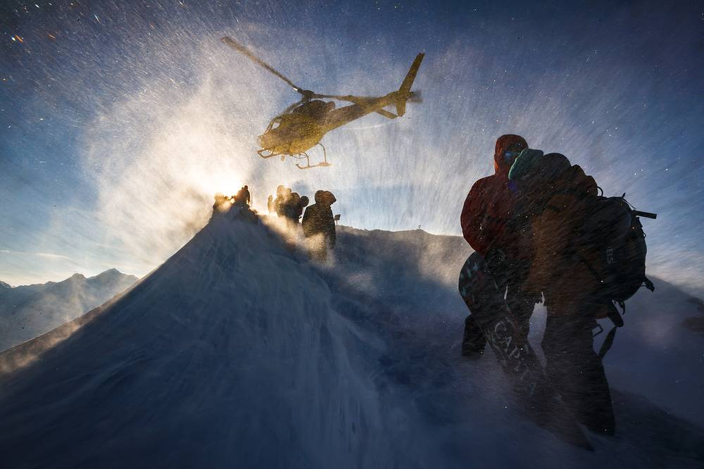 Technical staff take shelter as a helicopter takes off prior to the Nendaz Freeride skiing and snowboard competition, a Freeride World Tour Qualifier event, on the Mont Gond in Nendaz, Switzerland, March 21