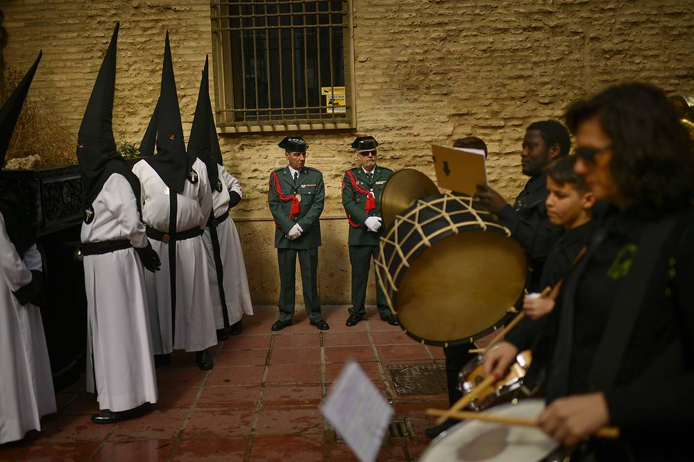 """Spanish Civil Guards, penitents and musicians take part in the procession of the """"Exaltacion de La Santa Cruz"""" brotherhood, during Holy Week in Zaragoza, Spain"""
