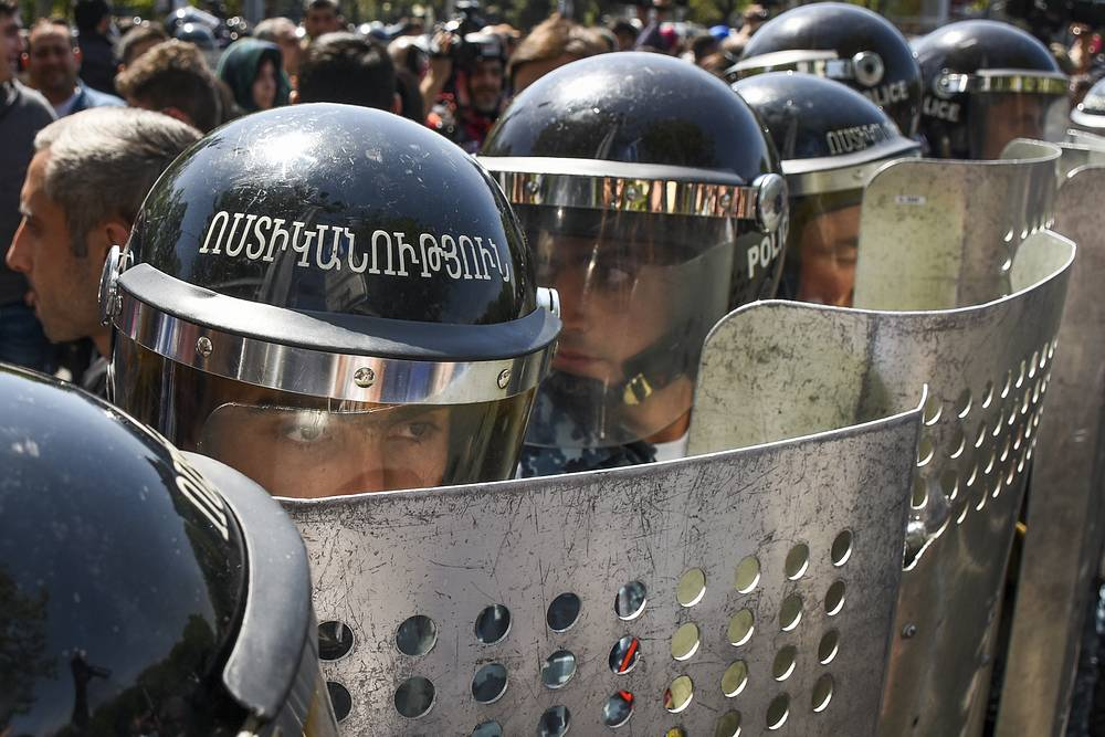 Riot police block opposition demonstrators protesting the former president's pursuit of the prime minister's seat in Yerevan, April 18