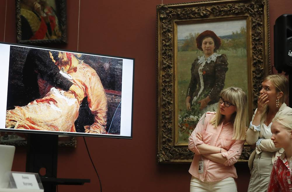 Visitors stare in shock at a monitor depicting the damage done to Ilya Repin's masterpiece 'Ivan the Terrible and His Son Ivan on November 16, 1581' at the Tretyakov Gallery in Moscow, May 28. A guest seriously damaged it on May 25, having broken protective glass of the painting by smashing it with a metal bar