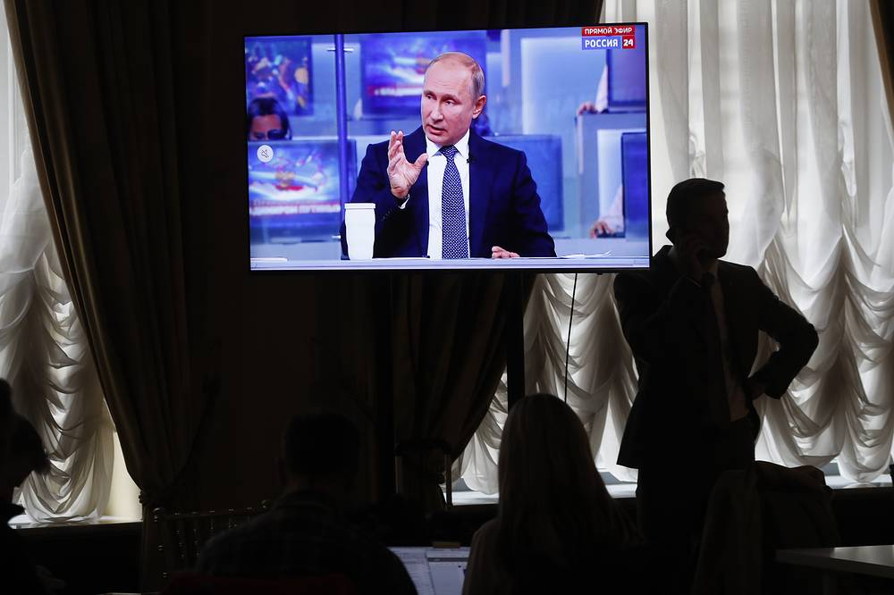 Journalist speaks on the phone while Russian President Vladimir Putin gestures answering a question during his annual Q&A session in Moscow