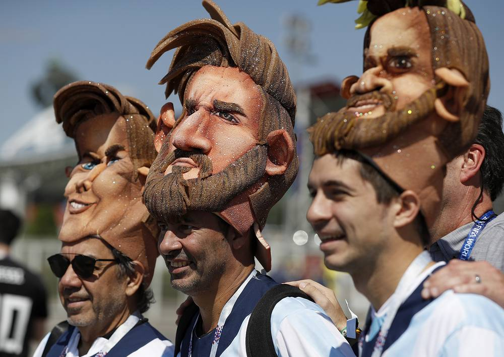 Argentinian fans pose for a photo wearing the mask of Lionel Messi near the Spartak Stadium in Moscow