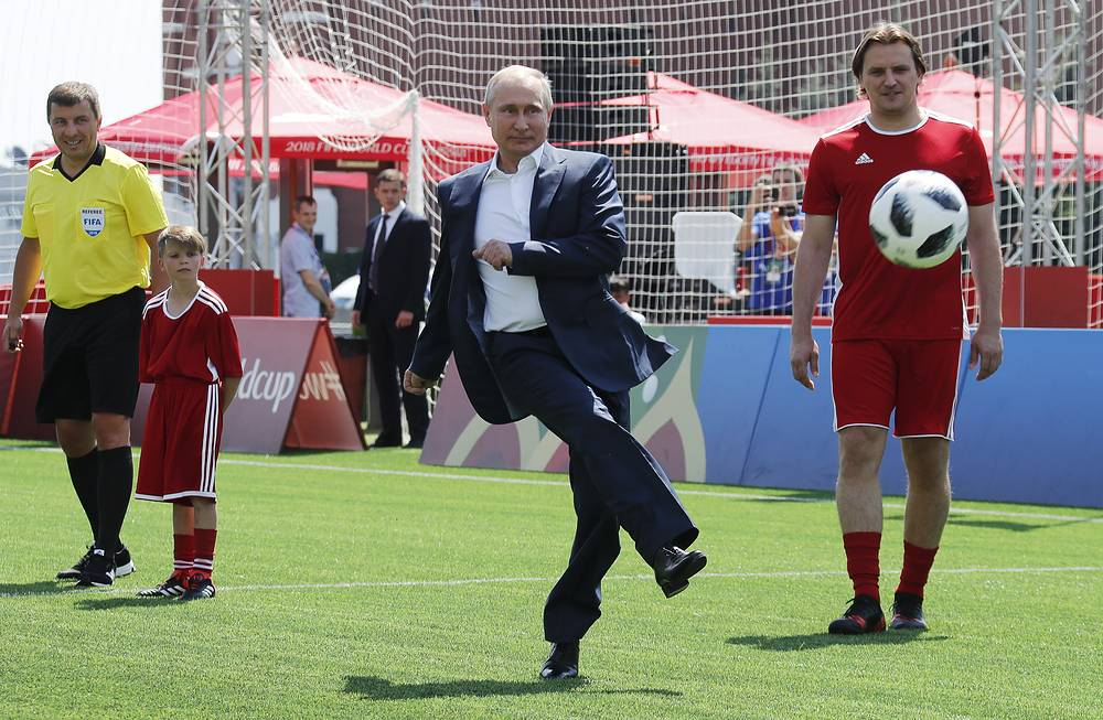 Russia's President Vladimir Putin launches a football into the air with a solid kick while visiting the 2018 FIFA World Cup Football Park in Red Square, June 28