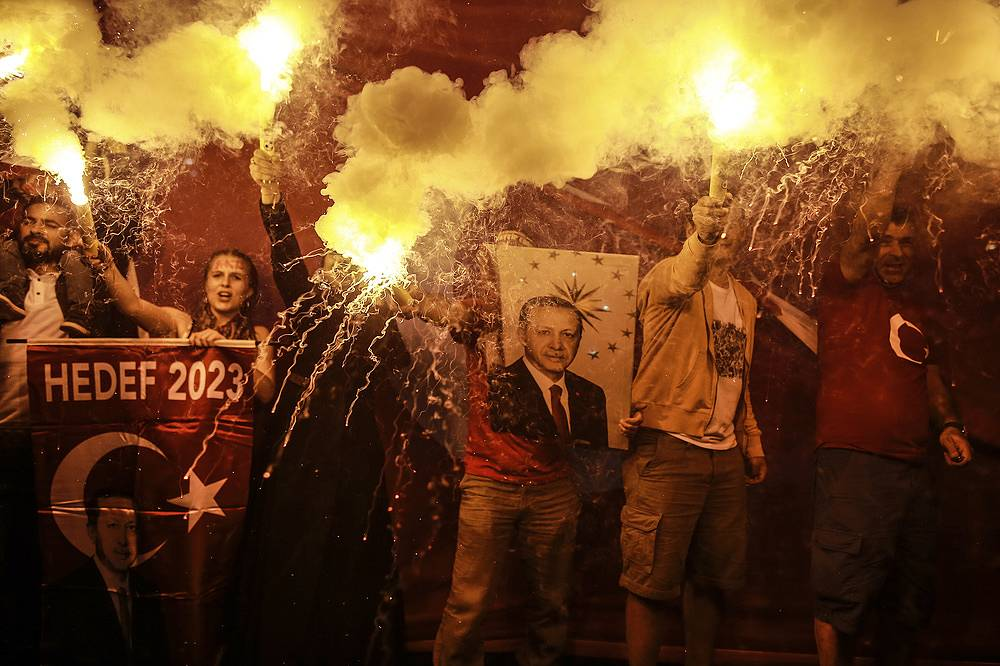 Supporters of Turkey's President and ruling Justice and Development Party, or AKP, leader Recep Tayyip Erdogan light flares during celebrations outside the party headquarters in Istanbul, June 24. Erdogan won in the presidential race, avoiding a second-round runoff vote