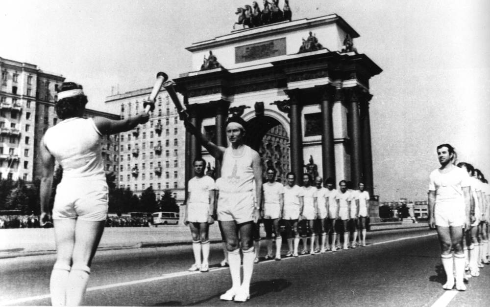 Former Soviet Olympic athlete Marina Koshevaya lighting her torch with the Olympic flame from another Soviet athlete in front of Moscow's Arch of Triumph on Kutuzovaky Avenue, July 18, 1980, shortly after the arrival of the Olympic torch in the Soviet capital. Almost 5,000 runners brought the flame from Greece to the outskirts of Moscow
