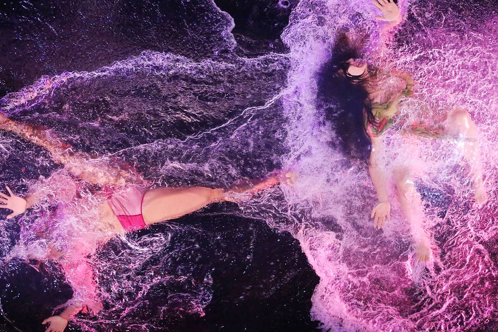 Performers dance in a water basin at a press call for Fuerza Bruta Wayra show at FB Theater of Jamsil Sports Complex in Seoul, July 18
