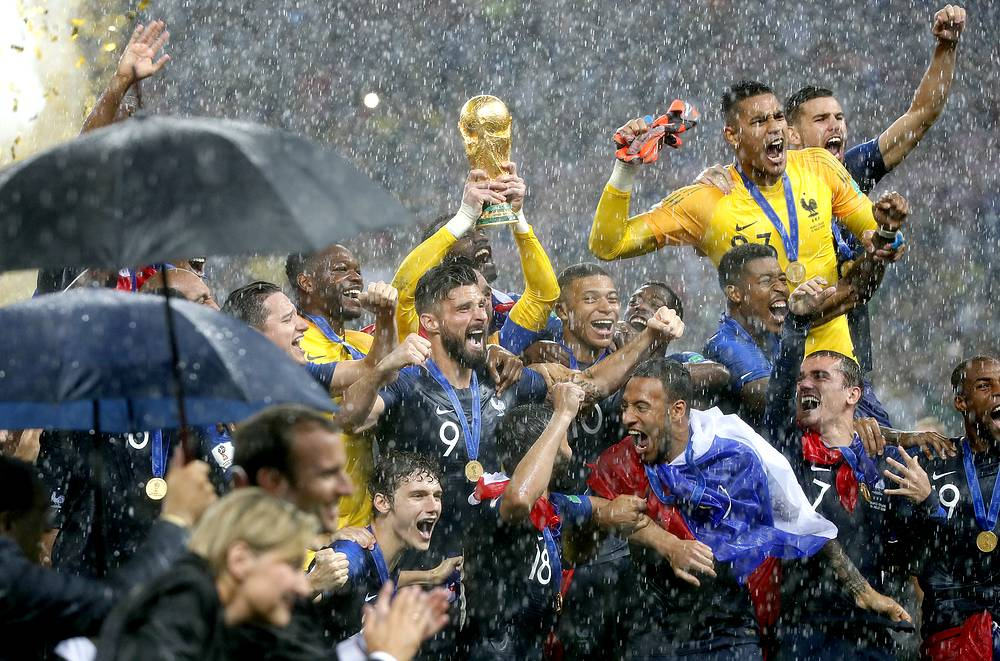 Team France celebrates win by brandishing the FIFA World Cup trophy during a heavy downpour after the FIFA World Cup 2018 final between France and Croatia in Moscow, 15 July